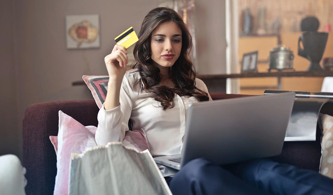 Woman sitting with laptop, bankcard in hand, ready to make a purchase.