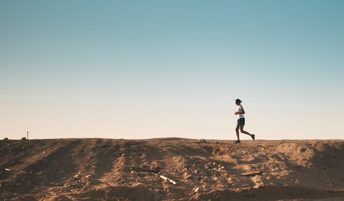 Sideways shot of a person running from right to left on a field soil.