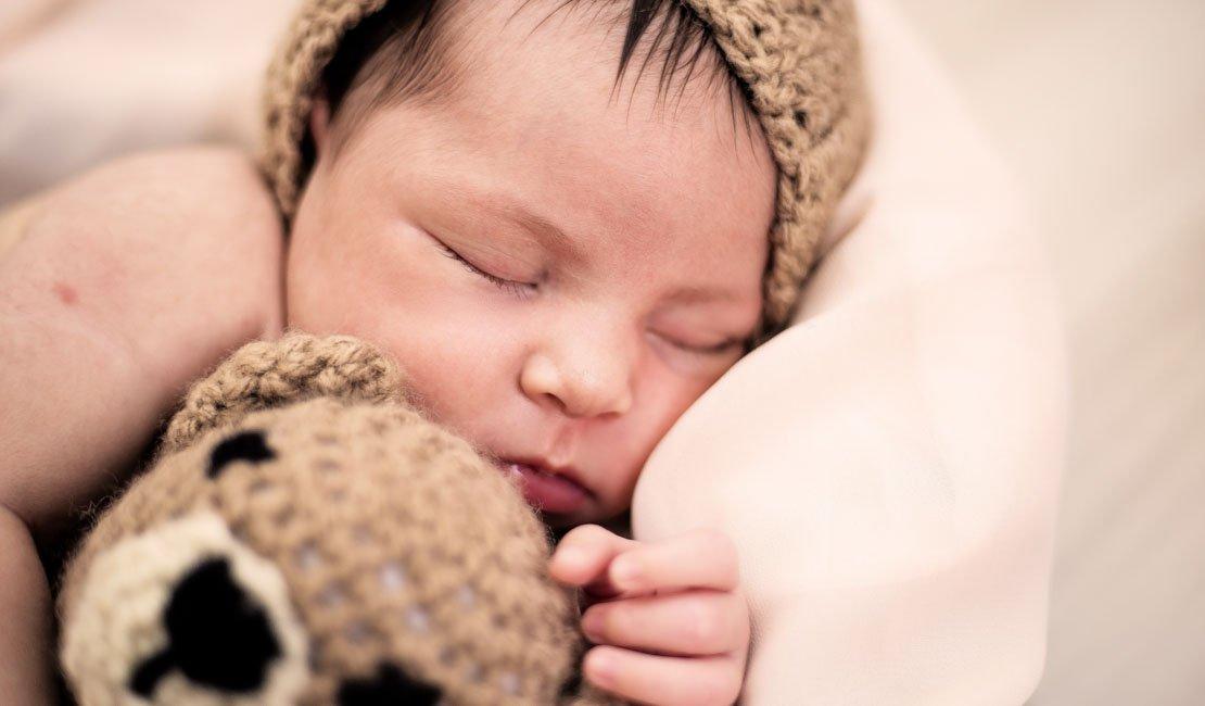 A baby sleeping with a teddy bear.