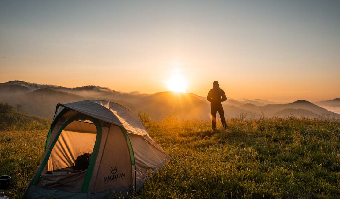 A tent in a field. In the background is a man overlooking mountains and hills whilst the sun is rising/setting.