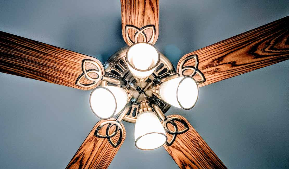 Ceiling fan with brown wooden blades up against a grey-blue ceiling.