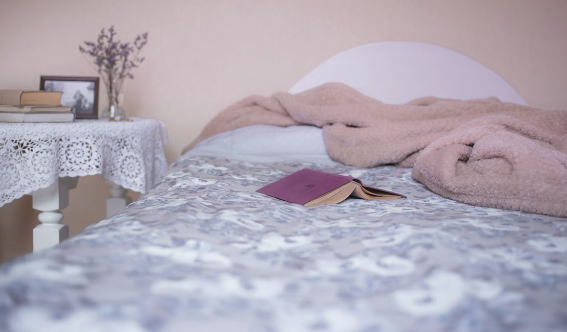 Bed and bedside table. Pink and blue tones in the picture. A book is open in the bed.