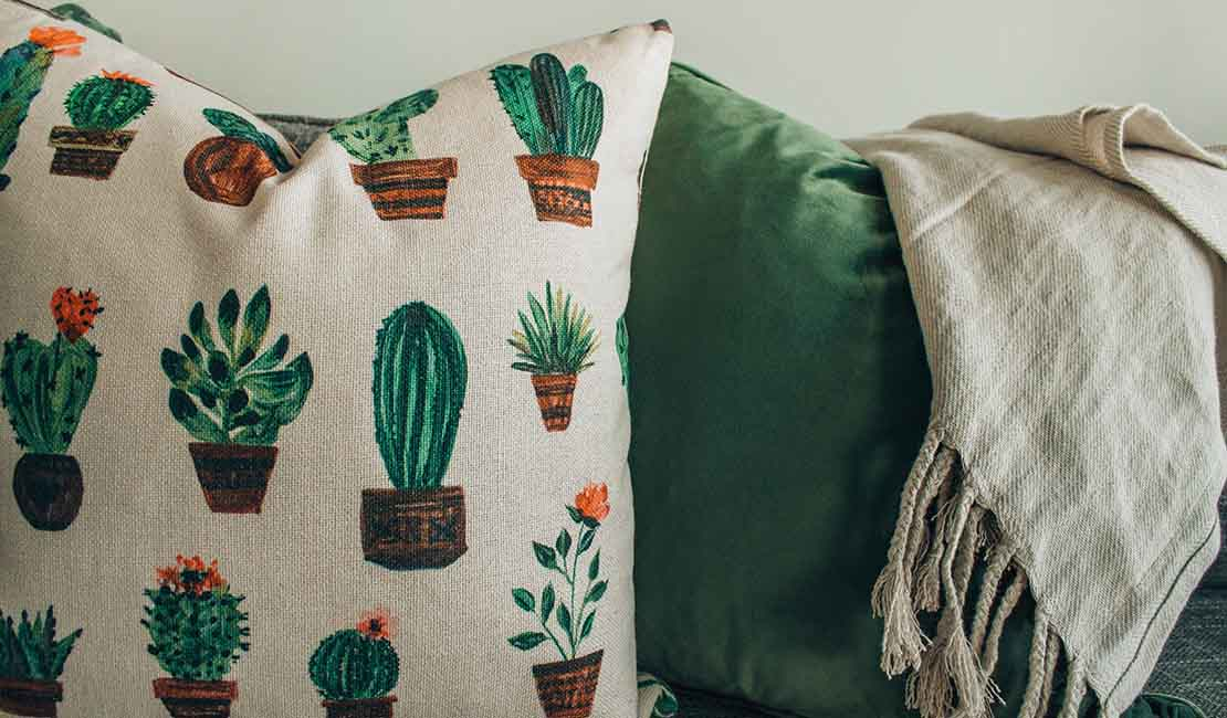 Natural colours bedroom accessories. Green pillow, cacti pillow, beige throw.