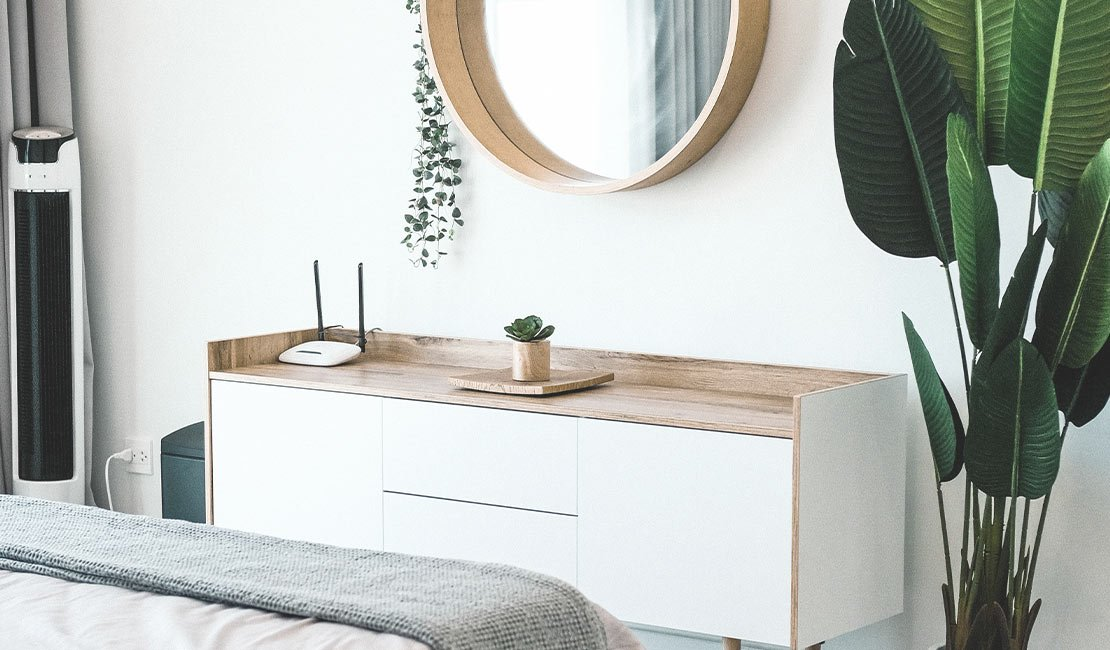 Vanity table with circular mirror against the wall. Large plant next to vanity table.