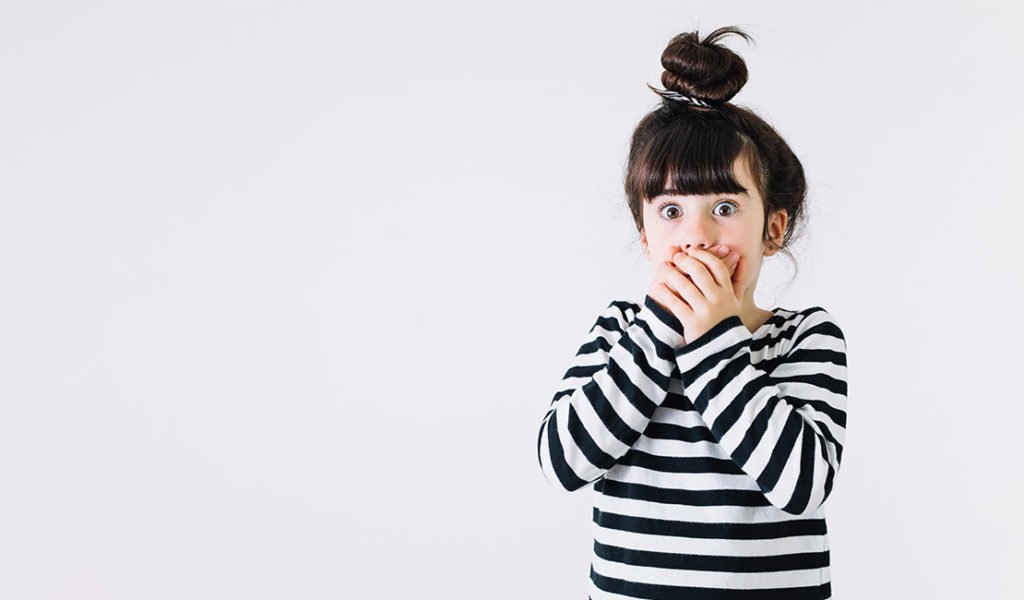Little girl with brown hair in striped shirt with hands covering her mouth as if she's shocked