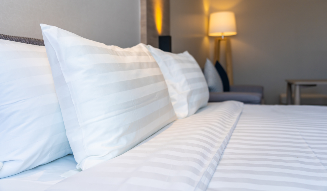 Crisp white bedding on a beautifully made bed.