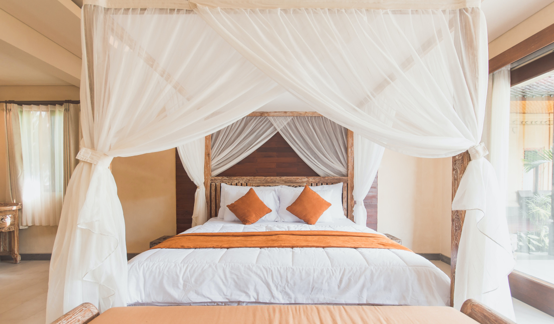 4 poster beds are luxurious and grand. They require large rooms, like this one with its glass doors and spacious floor.