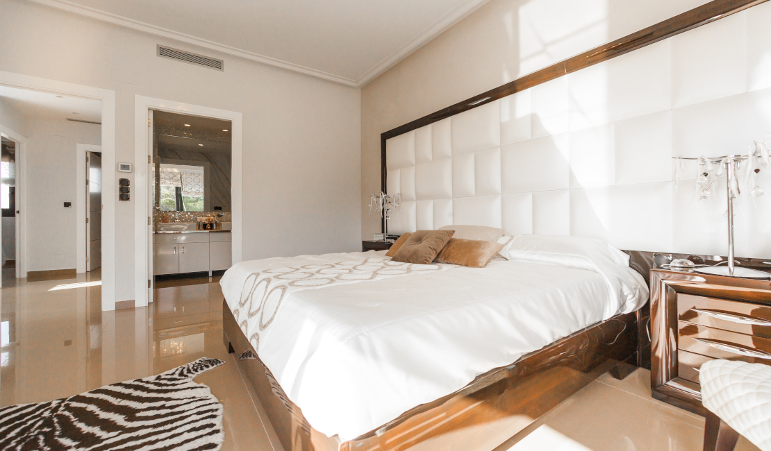 Leather headboards, like the large white one in this picture, are imposing and stylish.