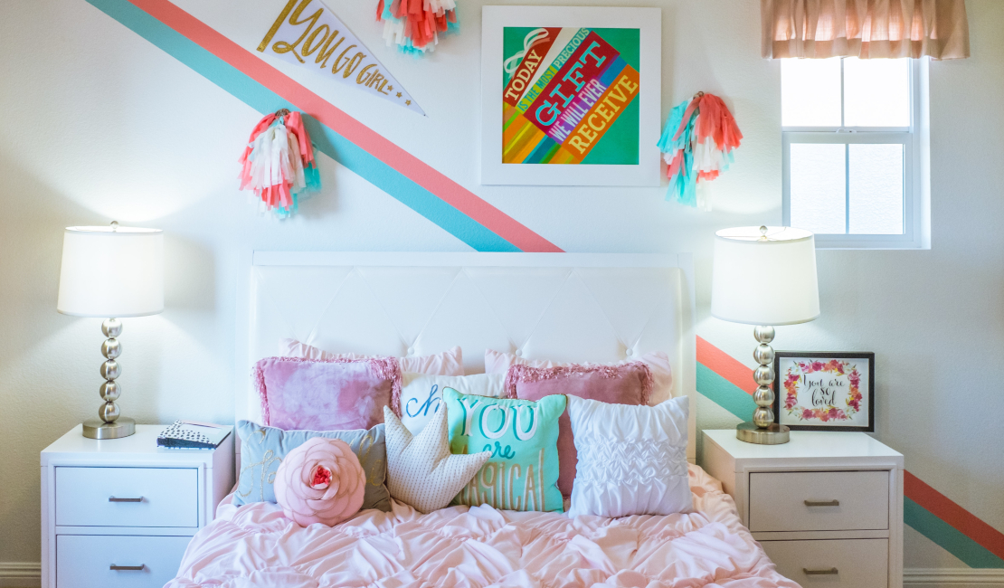 Teens can still be very pink and frilly, like this bedroom here with its pink comforter, stacks of pillows and pom-poms hanging on the wall.