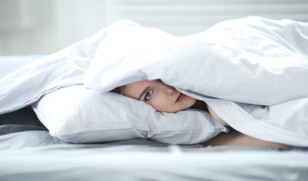 Woman nestled up in white bedding.