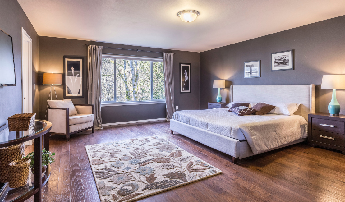 Bedroom with a wooden floor and large window overlooking some trees. The inside of the bedroom showcases a lot of bedroom furniture - a chair in one corner, a large bed against the opposite wall and a chest of drawers next to the bed.