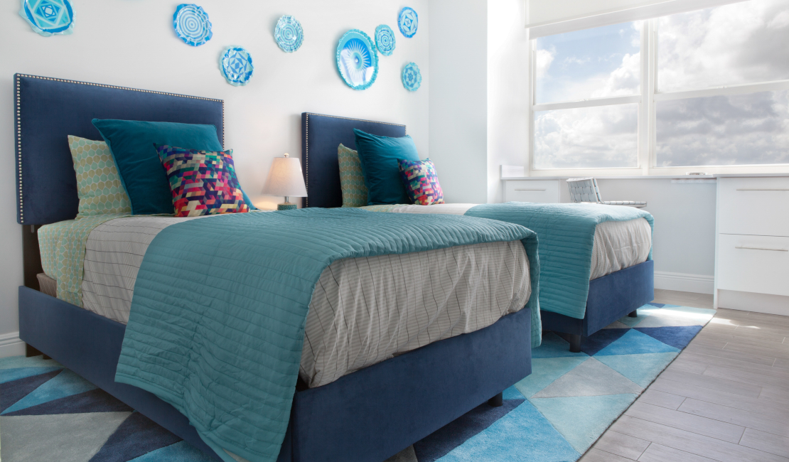 Blue ceramics against the wall, coupled with blue pillows and throws give this room a distinct coastal feel.