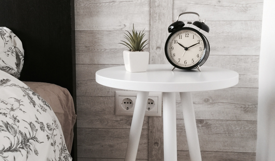 Next to the single bed, there is a bedside table with a clock and some succulent plants on it.
