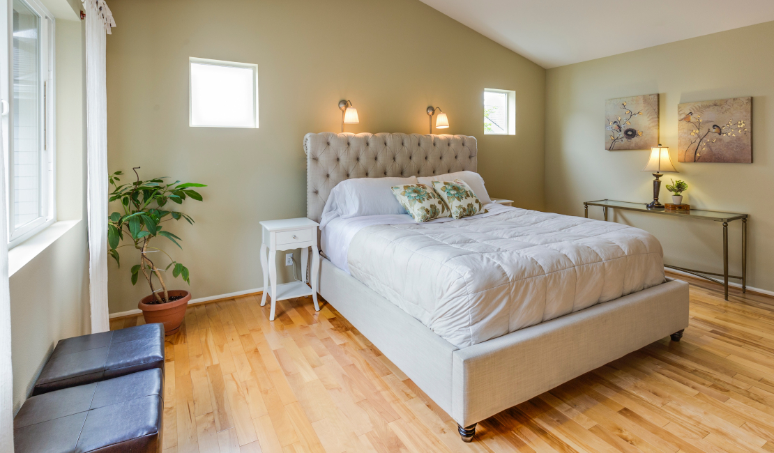 An XL double bed with white covers and an upholstered headboard set against a beige wall. The large leafed plant in the corner picks up the wooden floor beautifully.