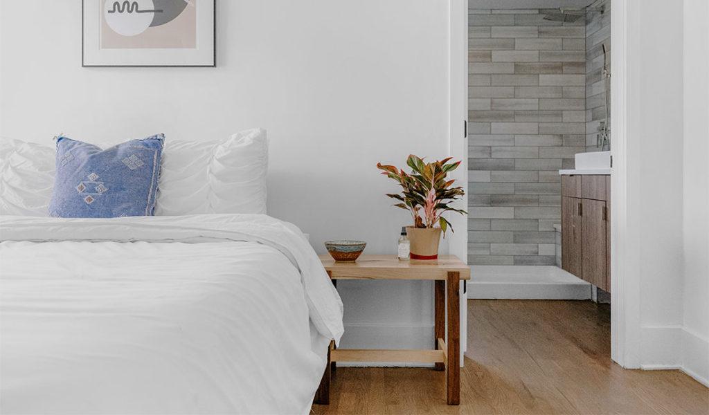 wooden bedside pedestal nxt to made up bed