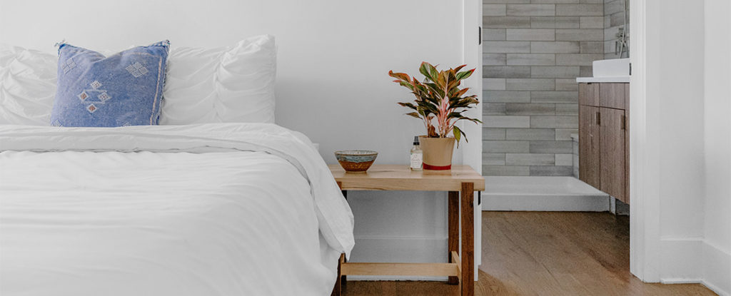 wooden bedside pedestal nxt to made up bed