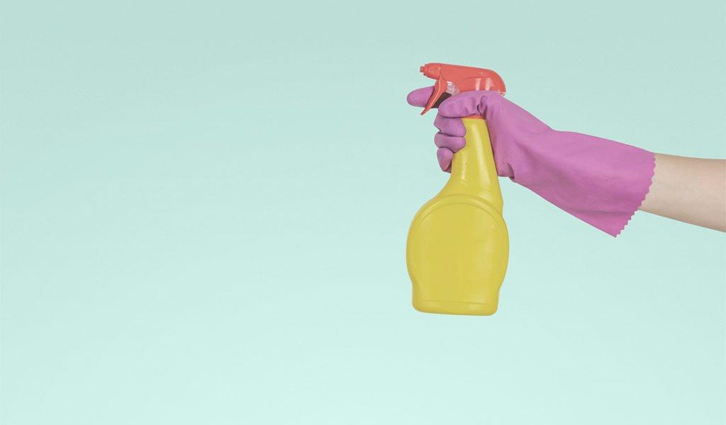 Gloved hand holding a spray bottle