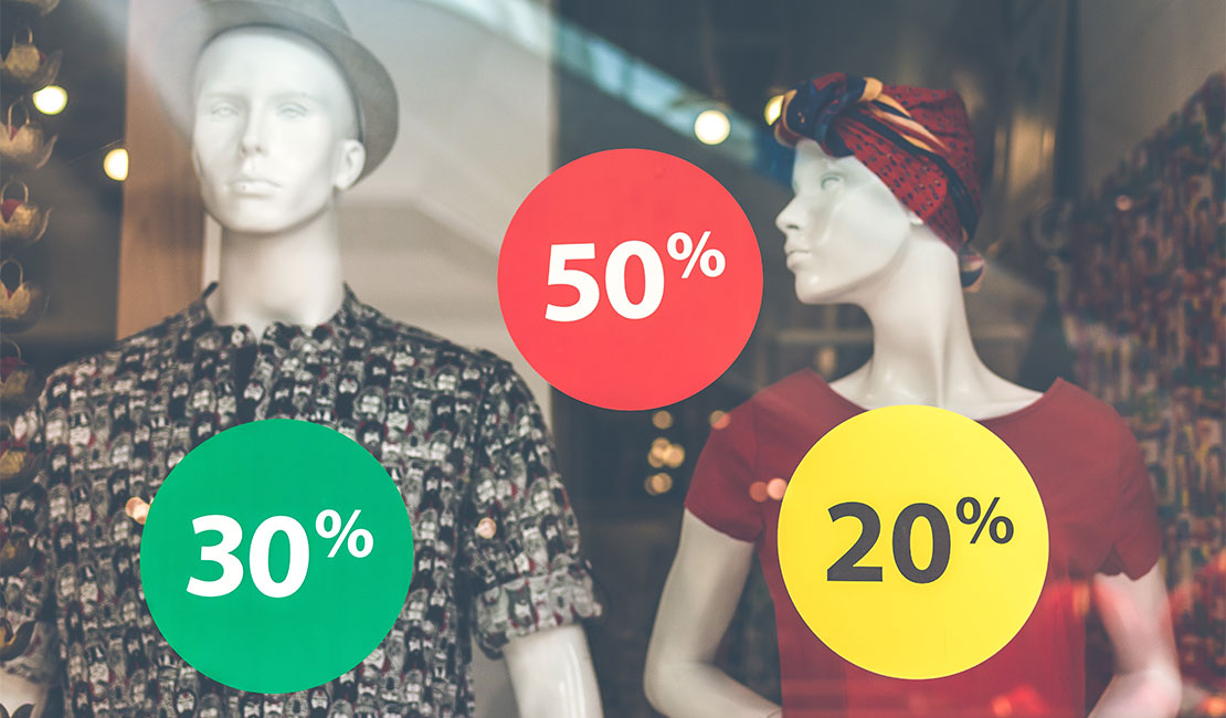 Mannequins in store window with 20%, 30% and 50% sale signs