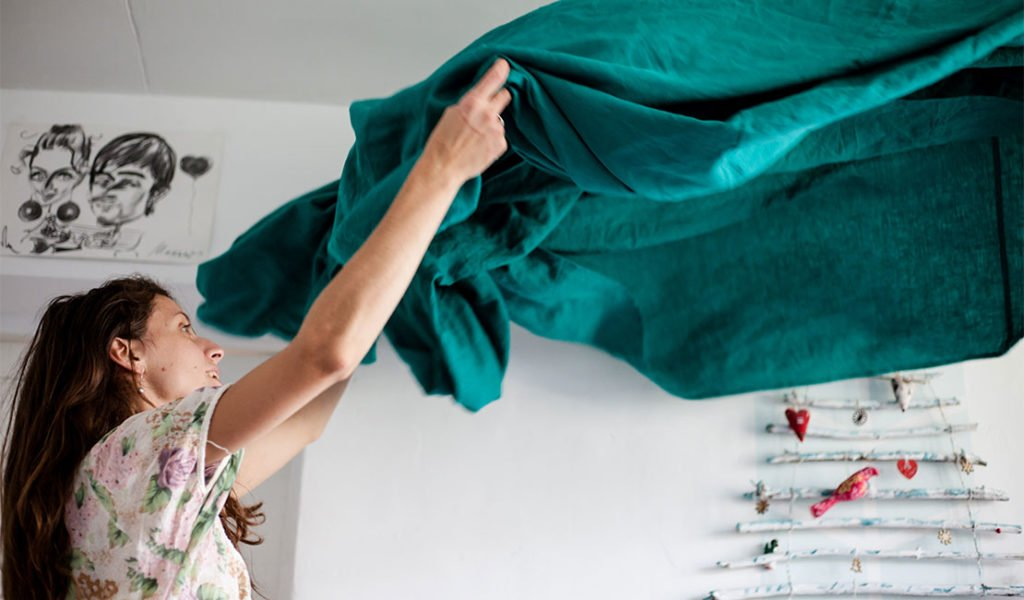 Woman shaking a teal sheet in the air