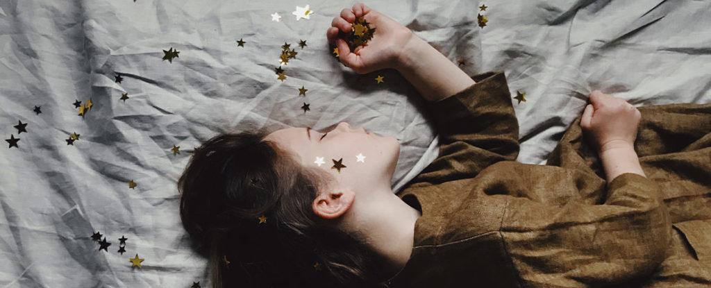 Little girl sleeping on a grey sheet/duvet wearing a brown dress, holding golden stars in her hand.