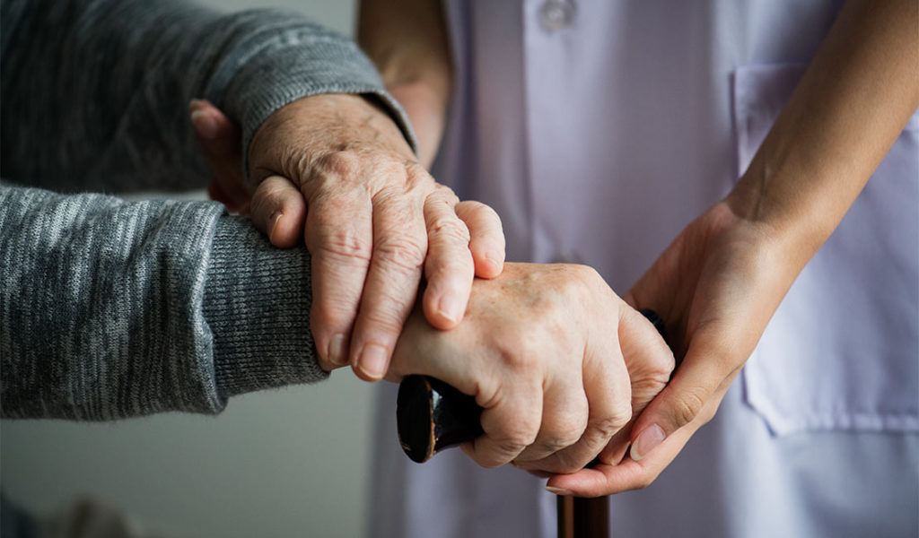 a set of young hands supporting an older person's hands