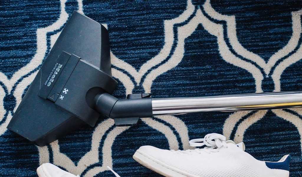Vacuum and white sneaker on navy and white geometric print rug